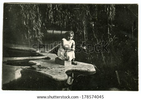 """MOSCOW, USSR - CIRCA 1960s : An antique photo shows young girl sitting on the bank of a pond. """"Soviet people"""" series - stock photo"""