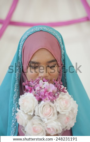 Moslem Asean Bride holding a flower - stock photo