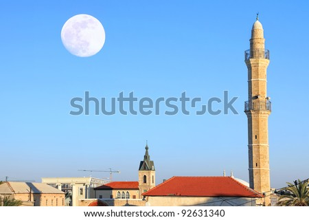 Mosque and roofs of the old city Yafo on the moonrise background - stock photo