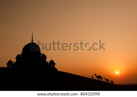 mosque in desert with camels silhouette - stock photo