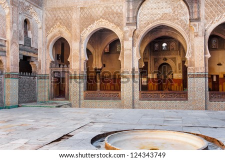 Mosque interior courtyard featuring elaborate tile, wood and plaster decoration .  Location: Fes, Morocco - stock photo