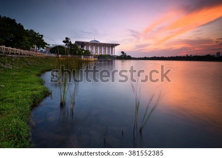 Mosque of Tuanku Mizan Zainal Abidin with its nature surrounding and nice colorful sunset sky. Focus on the mosque building with some soft focus and motion blur due to long exposure.
