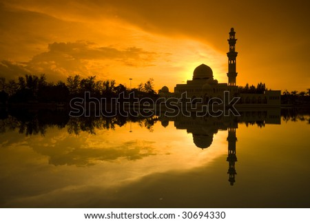 mosque silhouette during sunset with reflection - stock photo