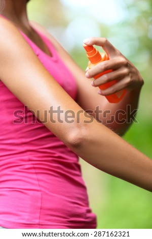 Mosquito repellent. Woman spraying insect repellents on skin outdoor in nature using spray bottle in forest. - stock photo
