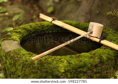 Moss-covered Japanese stone water basin with bamboo ladle.