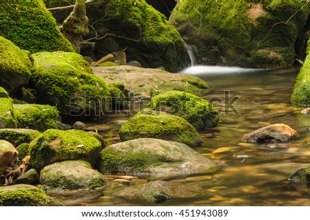 Moss covered rocks near little waterfall in rains forest, Thailand. - stock photo