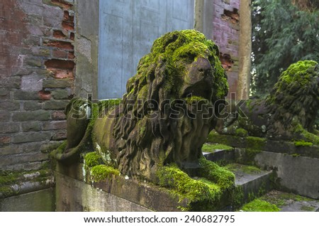 Moss-covered stone sculptures of lions in the old park. Italy. - stock photo