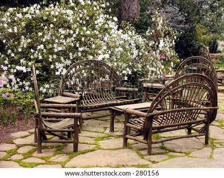moss lined stone patio with rustic wooden furniture - stock photo