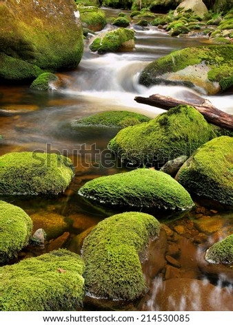 Mossy boulders in curved mountain river. Broken trunk on blocked at stream bank above bright blurred waves of clear water. - stock photo