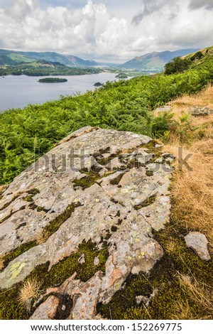 Mossy rock looking over to Derwent Water - stock photo