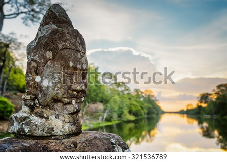 Mossy stone face Asura on causeway near South Gate of Angkor Thom in Siem Reap, Cambodia. Beautiful sunset over ancient moat in background. Angkor Thom is a popular tourist attraction. - stock photo