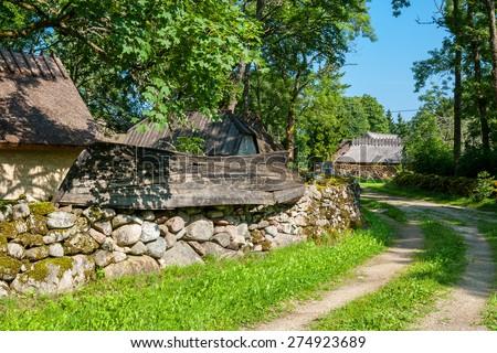 Mossy stone fence and old boat as decoration. Koguva village, Saaremaa island, Estonia, Europe  - stock photo