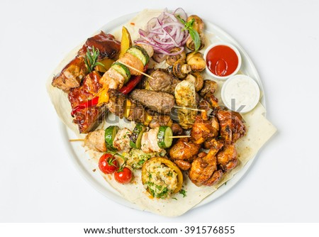 Most meat dish - pork ribs, chicken legs, beef kebabs, sausages, grilled mushrooms, potatoes, tomatoes and sauce. The best choice for a beer. Close-up in white plate on a white background top view. - stock photo