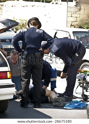 MOSTA, MALTA - APR16 - An injured cyclist receives first aid from ambulance crew and police on April 16, 2009