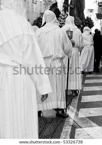 MOSTA, MALTA - APR 02: Hooded men in white habits dragging chains during the Mosta Good Friday procession in Malta April 02, 2010 - stock photo