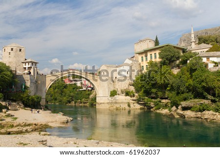 MOSTAR, BOSNIA AND HERZEGOVINA- SEPTEMBER 24: Tourists Enjoying Views of the Old Bridge While Others Walk Across the Historic Bridge On September 24, 2010 in Mostar, Bosnia and Herzegovina