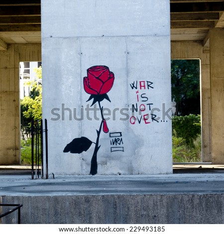 MOSTAR, BOSNIA, SEPTEMBER 30: A local artist has painted  a red rose on a wall. A tear rolls from a prickle to say that the war is not over in Bosnia., on september 30, 2014,  in Mostar, Bosnia. - stock photo