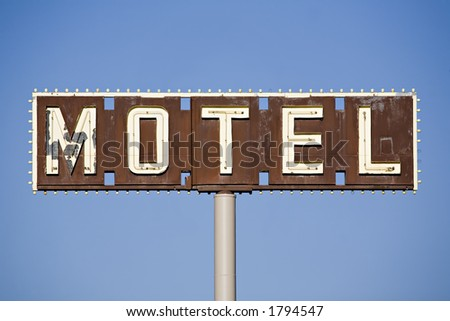 motel sign - old sign in disrepair against blue sky - stock photo