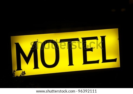 Motel sign shows the way to a motel at the street - stock photo