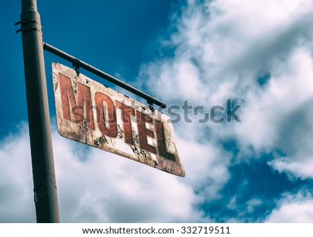 Motel Vintage Rusted Sign. Old rusted sign hanging off the side of an old country road. Motel sign. - stock photo
