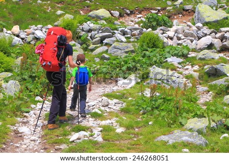 Mother accompanies young kid on the mountain trail during backpacking trip  - stock photo