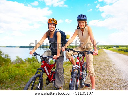 Mother and a daughter cycling near the lake