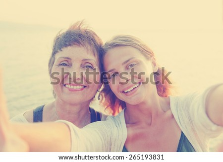 mother and adult daughter are doing Selfe on the beach - stock photo