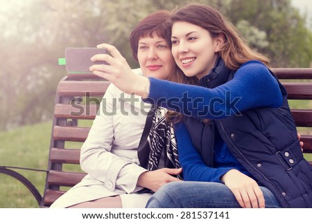 mother and adult daughter are doing Selfe outdoors - stock photo
