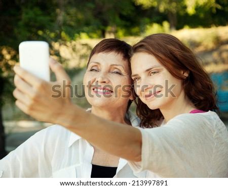 mother and adult daughter are doing selfie by mobile phone in summer  - stock photo