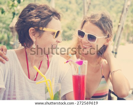 mother and adult daughter drink cocktails in the cafe - stock photo