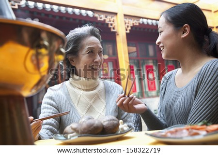 Mother and adult daughter enjoying traditional Chinese meal in restaurant - stock photo