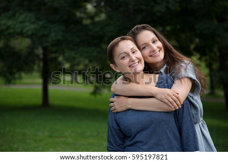Mother and adult daughter hugging and having fun together in the park outdoor in summer. Portrait of happy women smiling and looking at the camera.