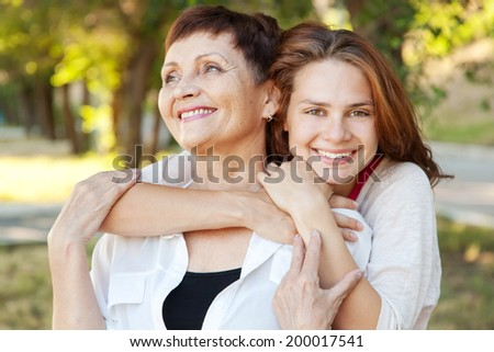 mother and adult daughter in the park, family portrait - stock photo