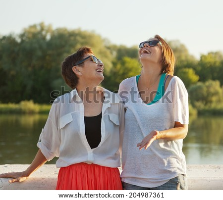 mother and adult daughter in the summer park, family portrait  - stock photo
