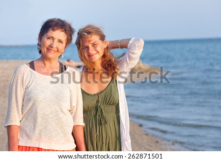 mother and adult daughter on sea shore, family portrait - stock photo