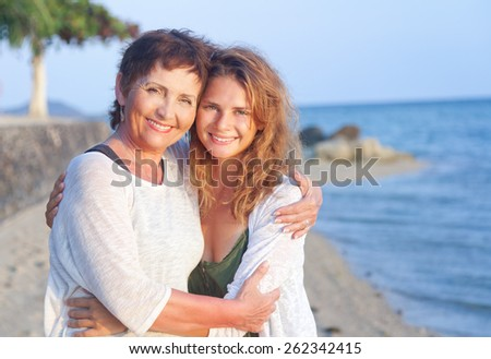 mother and adult daughter on the sea shore, family portrait - stock photo
