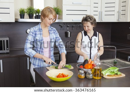 Mother and adult daughter preparing a salad in the kitchen in her house. - stock photo