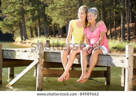 Mother and adult daughter sitting by lake - stock photo