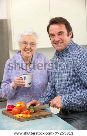 Mother and adult son preparing meal together - stock photo