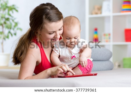 mother and baby are looking to play tablet computer on the couch at home - stock photo