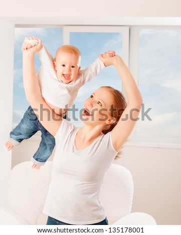 Mother and baby are playing active games, do gymnastics and laughing at home against the window and the sky - stock photo
