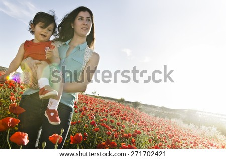Mother and baby at spring sunset backlight with sun flare and sky space - stock photo