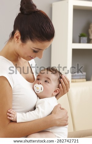 Mother and baby boy embracing, looking affectionate. - stock photo