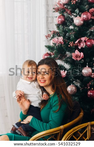 Mother and baby by the Christmas tree. Happy holidays. Christmas eve