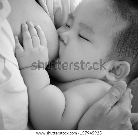 Mother and baby. Close up Asian mother breastfeeding baby boy in black and white tone. - stock photo