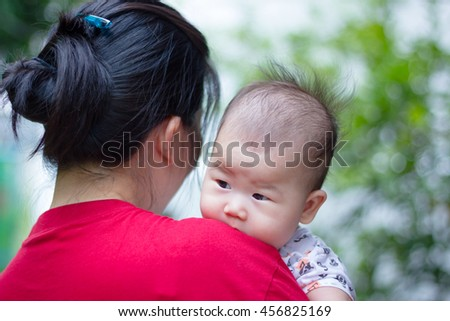Mother and baby, Closeup lovely asian girl resting on her mother's shoulder over blur nature background. Happy family spending time togetherness. Mother's Day celebration. - stock photo