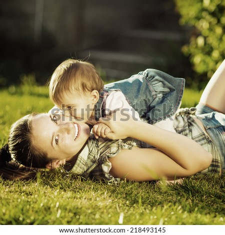 Mother and baby daughter are playing outdoors. Young mom and her cute little baby-girl are having fun in the sunny garden. Happy childhood and parenthood concept. Instagram style filter.  - stock photo