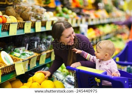Mother and baby daughter in supermarket buying fruits and vegetables - stock photo