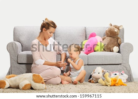 Mother and baby daughter playing in living room 2 - stock photo