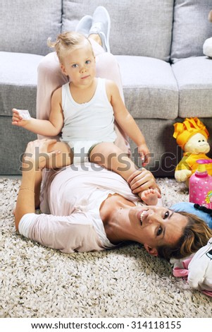 Mother and baby daughter playing in living room